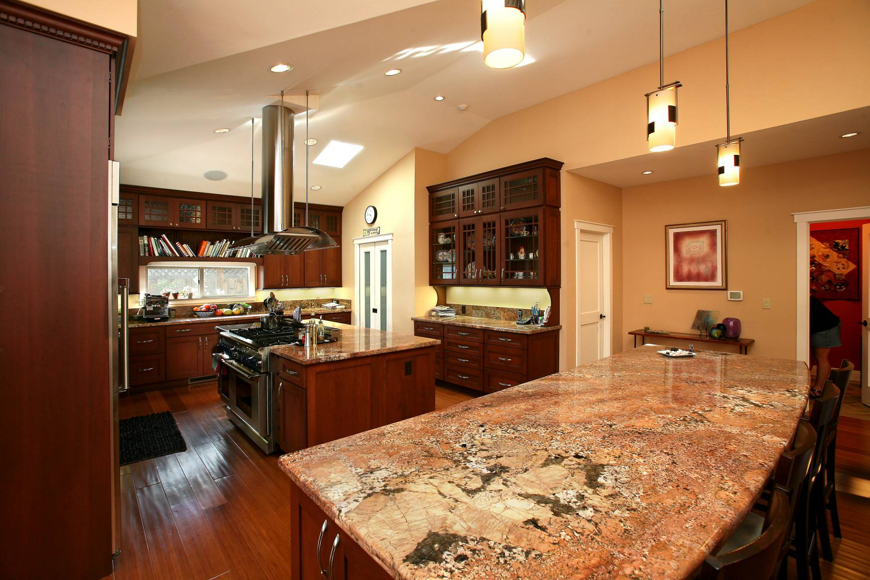 Large kitchen island with marble countertops wooden cabinetry